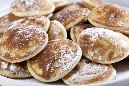 Dutch mini pancakes, or poffertjes, sprinkled with powdered sugar.