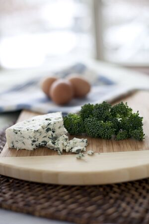Fresh broccoli, blue cheese, and eggs; ingredients for a quiche. photo