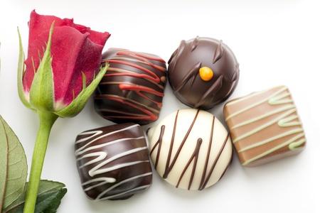 snoepjes: Een beetje romantiek met een rode roos en chocolade bon-bons. Stockfoto