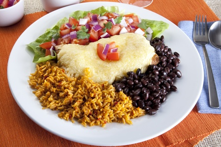 Burrito plate with a side of black beans rice and a fresh salad. Stock Photo