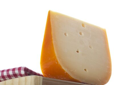 Wedge of Dutch cheese on cutting board form low angle