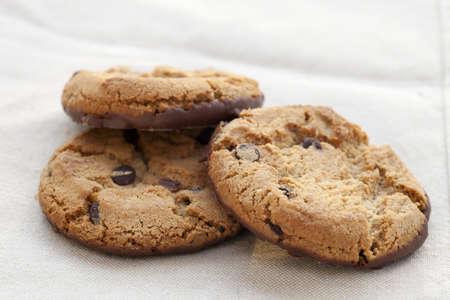 Three chocolate chip cookies on white linen cloth. Banco de Imagens