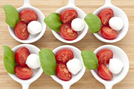Fresh mozzarella, cherry tomato and basil appetizers photographed from above.  .