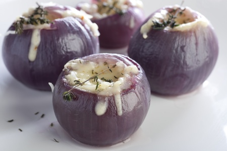 Close-up of stuffed red onions with chees and thyme leaves.   and thyme leaves.