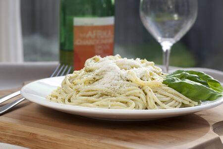 Gourmet pesto pasta dinner with fresh basil leaves.
