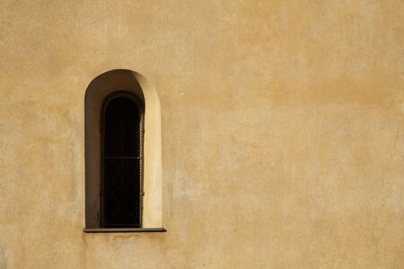 Long window and yellow stucco wal in direct sunlight. photo