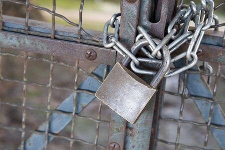 Worn padlock and chain securing gate. Stock Photo - 9178762