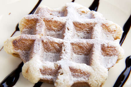 Closeup of waffle covered in powdered sugar.