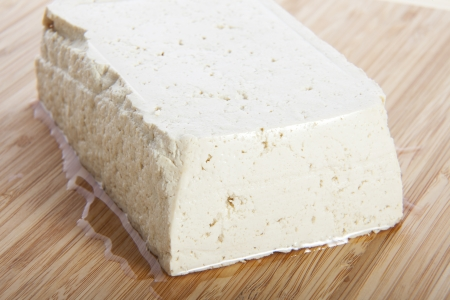 Block of fresh tofu on cutting block. Stock Photo