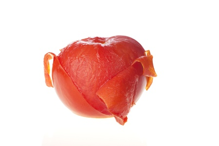 Isolated tomato, cooked and half peeled.