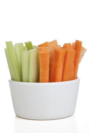 zanahorias: Bol de zanahoria y apio palos aislado en un fondo blanco.