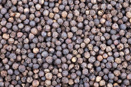 Black peppercorns food texture background.