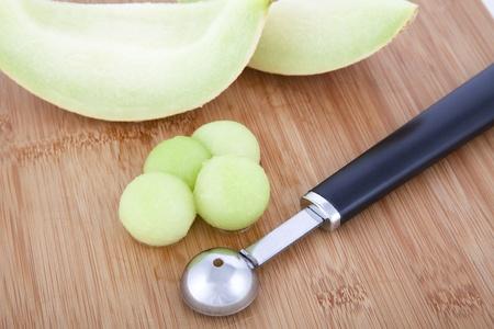 Fresh Honeydew melon balls on cutting board with melon baller Stock Photo