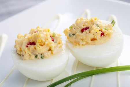 Two gourmet deviled eggs with chives garnish.