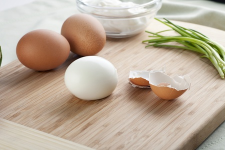 Peeled hard boiled egg with shells, two whole eggs and chives on cutting board. Lizenzfreie Bilder