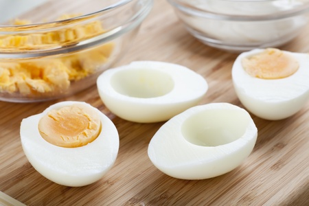 boiled: Two hard boiled eggs cut in half with yolk in bowl. Stock Photo