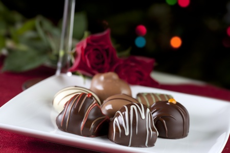 Gourmet chocolates on white plate with roses and sparkeling lights. Stock Photo