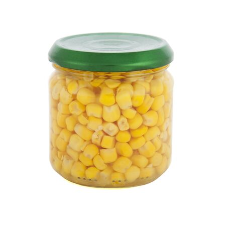 Glass jar of sweet corn with green lid on white background photo