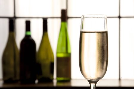 Glass of champagne in foreground with sepia tones and bottles in back ground. photo