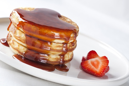 Pancakes covered in syrup with fresh strawberries. Stock Photo