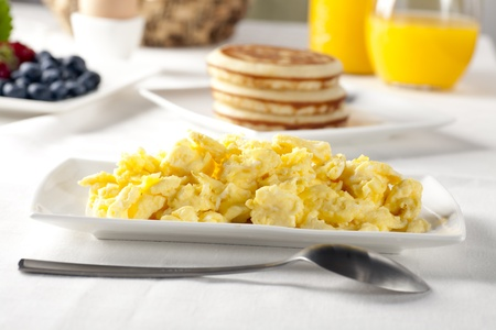 Fresh scrambled eggs and serving spoon on brunch table.
