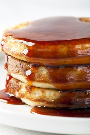 Close-up of stack of fresh pancakes covered in syrup.