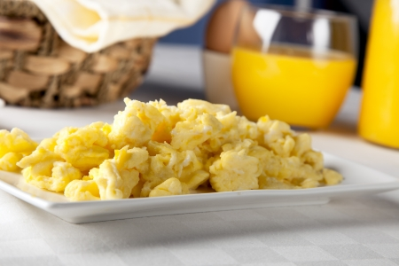 scrambled: Plate of fresh scrambled eggs with orange juice in the background