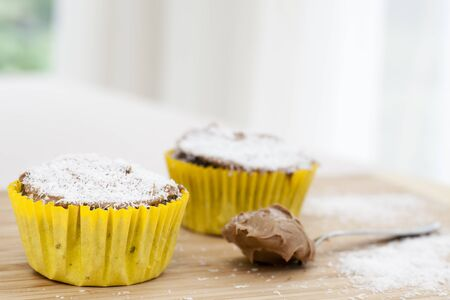 Two chocolate cupcakes sprinkled with coconut on cutting board with spoon and icing. Stock Photo - 10407045