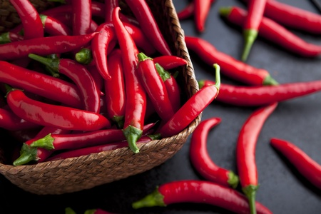 Fresh chili peppers in basket and on the table. Stock Photo
