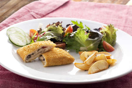 Vegetarian version of courdon blue with salad and rosemerry potatoes. photo