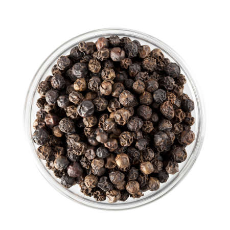 Black peppercorns in glass bowl, isolated and shot from directly above.