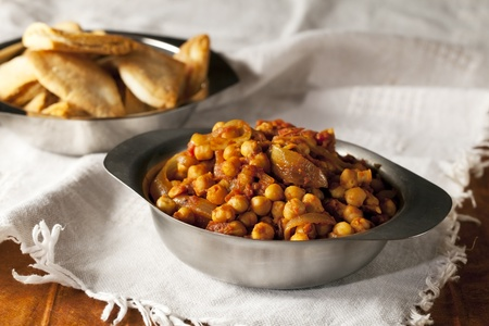 Fresh tomato and chickpea curry in metal bowl. Imagens