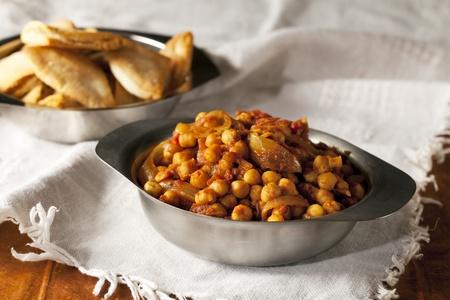 Fresh tomato and chickpea curry in metal bowl. Foto de archivo