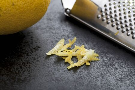 Lemon zest on black work surface with grater and lemon partially in frame. Stock Photo
