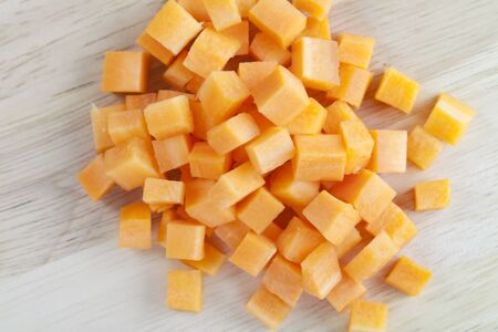 cubed: Brunoise or cubed carrots on wooden surface.