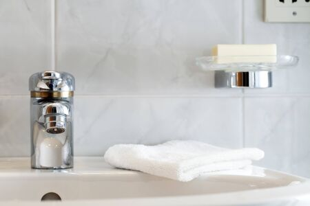 Bathroom faucet with washcloth and soap in soap dish. photo