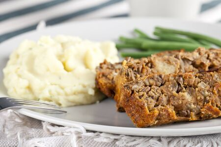 Vegetarian meal with lentil loaf, mashed potatoes and green beans.