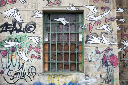 broken window in abandoned building covered with graffiti of birds photo