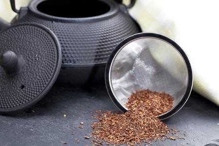 Dried rooibos tea leaves beside teapot