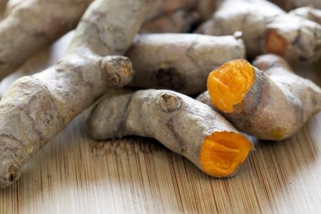 Turmeric root broken in half exposing orange root