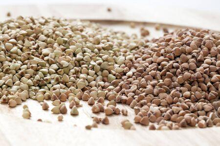 kasha: Untoasted and toasted buckwheat or kasha on a wooden plate