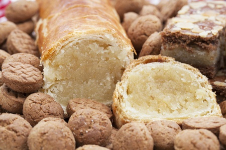 Dutch Christmas season treats, an almond roll surrounded by kruidnootjes and speculaas Stock Photo - 15635927