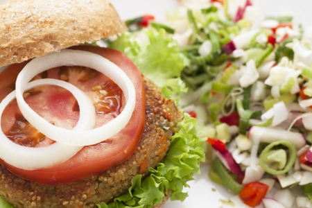 Delicious and healthy quinoa burger topped with a tomato slice and onions