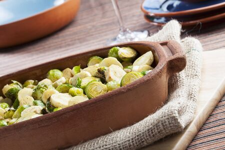 parsnips: Roasted parsnips and brussel sprouts in terracotta baking dish  Stock Photo