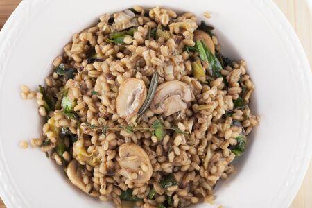 Healthy vegan barley dish with mushrooms collard greens, thyme and rosemary