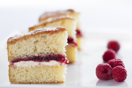 Victoria sponge cake with cream and jam filling, served with raspberries photo