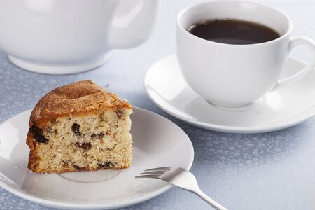 fruitcake: Slice of fruitcake made with raisins and cup of tea