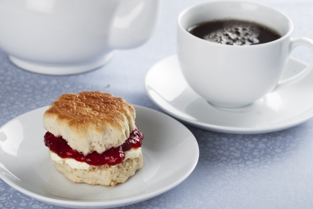 English scones with cream and strawberry jam with tea Foto de archivo