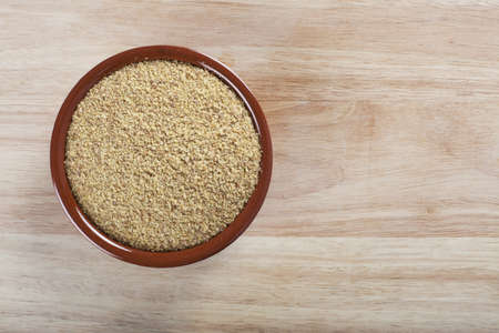 Bowl of wheat germ on wooden surface