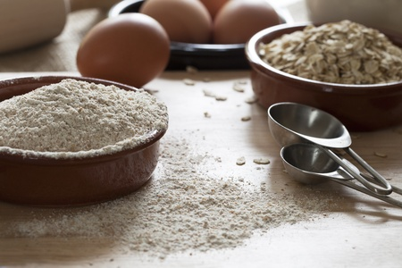 avena en hojuelas: Taz�n de harina de trigo integral y los copos de avena con cucharas de medir y los huevos en el fondo Foto de archivo